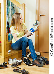 Long-haired blonde woman cleaning footwear