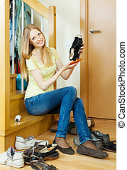 Long-haired blonde woman cleaning shoes