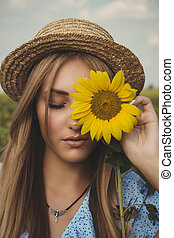Long-haired blonde young woman in a straw hat and blue dress on a field of sunflowers.