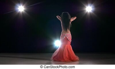 Long-haired brunette belly dancer girl dancing exotic dance movement on black, back light, slow motion