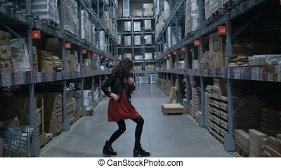 long haired brunette in brown dress dances in household shop...
