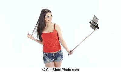 Long-haired brunette makes selfie using a monopod. Studio. White background
