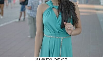 Long-haired brunette weared in the blue dress walking around...