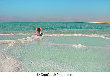 long-haired brunette woman sitting on a path of salt in the sea. The water surface of the Dead Sea in Israel with a view of the mountains of Jordan. Merging with nature.