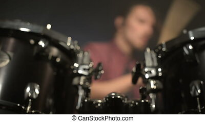Long-haired drummers play drum kit in a dark room on a black...