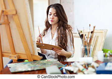 Long-haired female artist paints picture on canvas with oil ...