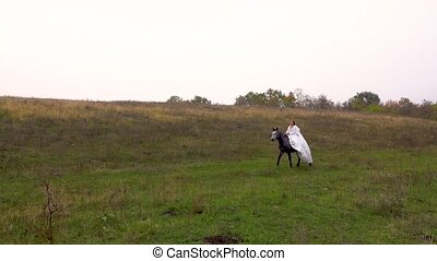 Long-haired female in white dress is riding horse along wood...