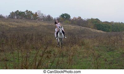 Long-haired female in white dress riding galloping horse ...