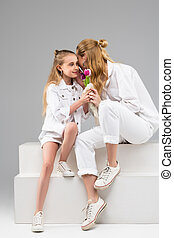 Long-haired tall girl presenting tulip bouquet to her little...