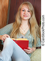 Long-haired female student reading book at home
