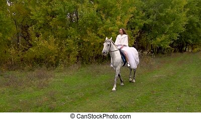 Long-haired fiancee in white dress is riding horse along ...