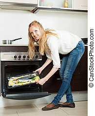 Long-haired girl cooking fish in oven