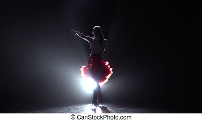 Long-haired girl dancing rumba on a dark background with light illuminator. Slow motion