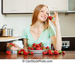 long-haired girl eating strawberry