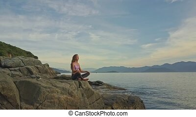 Long Haired Girl Meditates in Yoga Pose against Hills on...
