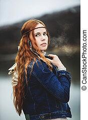 Long-haired girl on lake shore