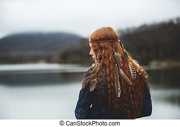 Long-haired girl on lake shore
