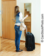 Long-haired girl with luggage looking in mirror