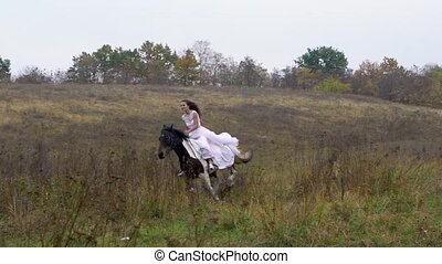 Long-haired horsewoman in wedding dress riding galloping ...