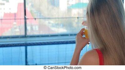long haired lady enjoys delicious orange beverage closeup - ...
