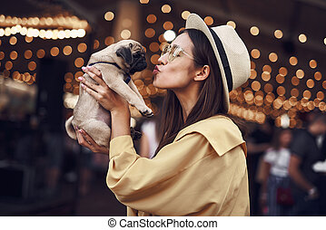Long haired lady kissing her puppy while holding it in two ...
