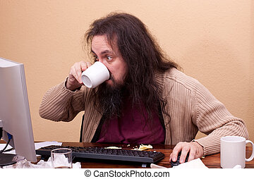 long haired man at dirty desk drinks a coffee