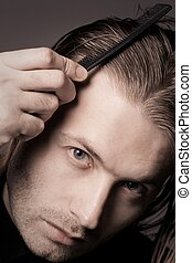 Handsome long-haired man with serious face combing his hair
