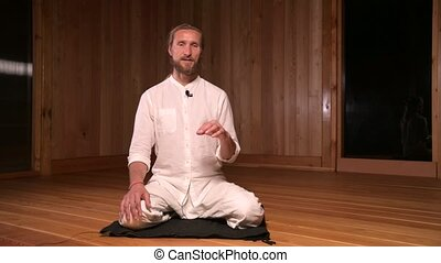 Long-haired man qigong and yoga practitioner sitting in lotus position and talking about practice in dark room of meditation hall.
