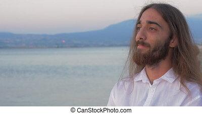 Long-haired man with beard on the beach