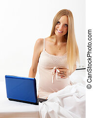 long-haired pregnant woman with laptop