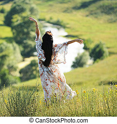 Long haired slender girl in light dress on the hill above the river viewed from behind