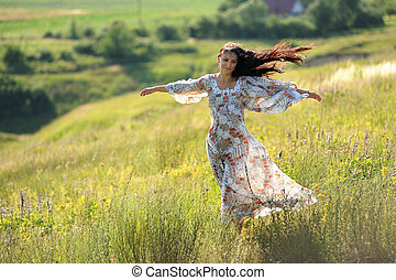 Long haired slender girl in light dress on the hill in windy summer day