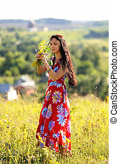 Long haired slender girl in red dress on the hill above the river with flowers