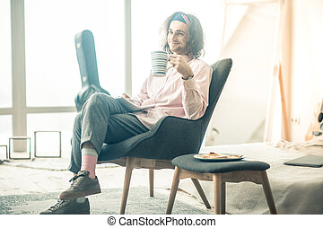 Cheerful good-looking man chilling in spacious armchair and carrying cup