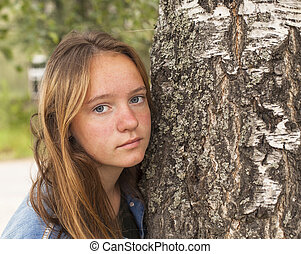 Long haired teen girl in the Park closeup portrait near a tree.