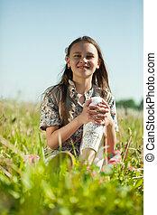 teen girl sitting in meadow