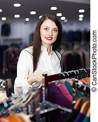 long-haired woman choosing clothes at store