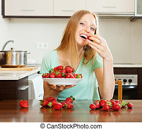 long-haired woman eating strawberry