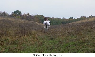 Long-haired woman in wedding dress riding galloping horse ...