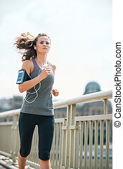 Long-haired woman jogging on bridge listening to music in...