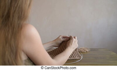 Long-haired woman knitting a scarf - Beautiful young blonde...