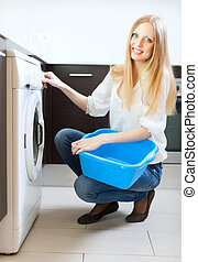 Long-haired woman using washing machine at home