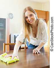 long-haired woman wiping the dust from table - Happy blonde...