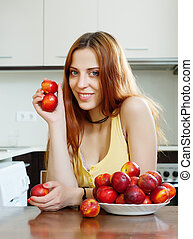 woman with nectarines in  kitchen