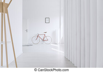 Long hall with clothes rack - Long, white hall with wooden...