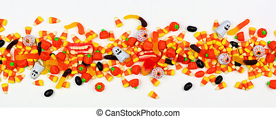Long Halloween border of scattered assorted candy, top view over white