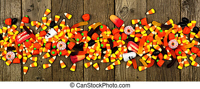 Long Halloween border of scattered assorted candy, top view over wood