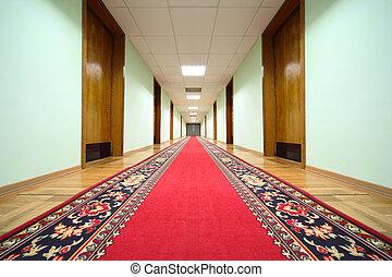 long hallway with brown wood doors, end of corridor, red carpet on floor