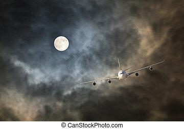Long-haul night flight through clouds in light of full moon