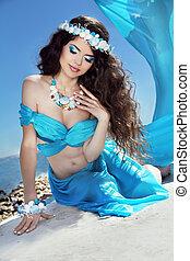 Long Healthy Hair. Beautiful brunette woman in blue silk luxury dress with sea jewelry.
